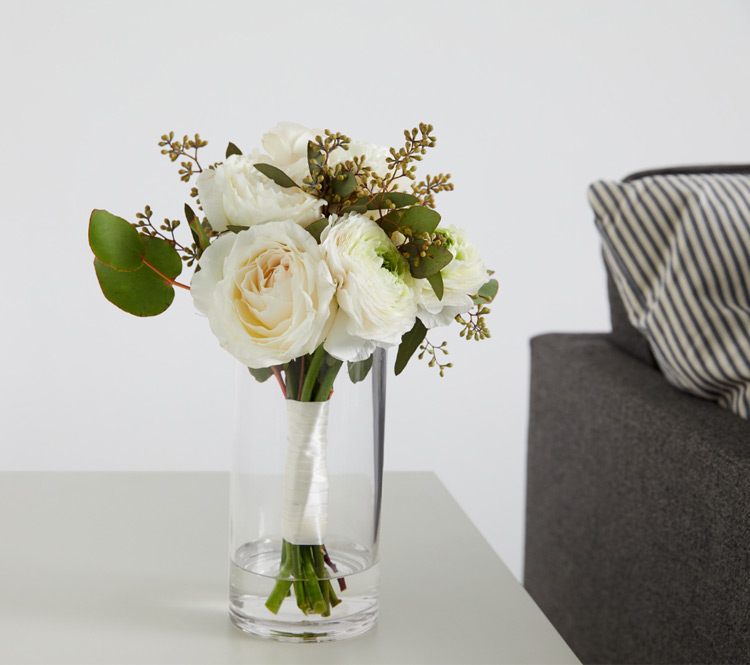 A vase of flowers next to a couch